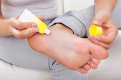 Woman applying cream on feet Royalty Free Stock Photo