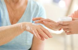 Woman applying cream on hand stock image