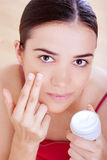 Woman applying cream on her face Stock Photography