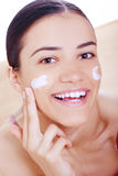 Woman applying cream on her face Royalty Free Stock Images