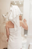 Woman applying cream on her face in bathroom Royalty Free Stock Images