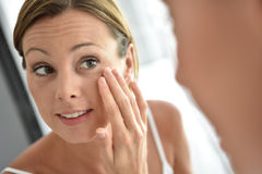 Woman applying daily cream on her face Royalty Free Stock Photos