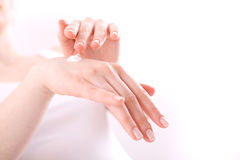 Woman applying cream on her hands Stock Image