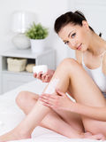 Woman applying cream on her leg Royalty Free Stock Photo