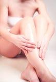 Woman applying cream on her legs stock image