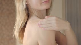 Woman applying cream on her shoulder.  stock footage