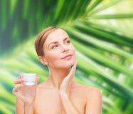 Woman applying cream on her skin Royalty Free Stock Image