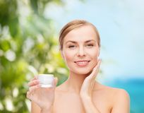 Woman applying cream on her skin Stock Photo