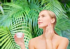 Woman applying cream on her skin Stock Photography
