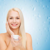 Woman applying cream on her skin Royalty Free Stock Photos