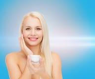 Woman applying cream on her skin Royalty Free Stock Photo