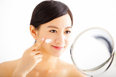 woman applying cream lotion on face Stock Photo