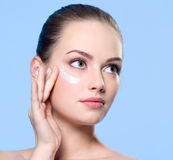 Woman applying cream on skin around  her eyes Stock Images