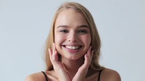 Woman applying cream to face, skincare concept.  stock footage