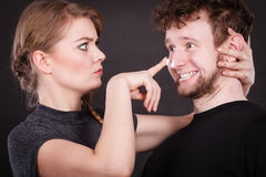 Woman applying cream to her man face. Protection and skincare. Stubborn girlfriend trying to apply cream on her boyfriend face. Man in uncomfortable situation Royalty Free Stock Photos