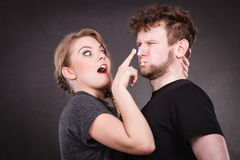 Woman applying cream to her man face. Protection and skincare. Stubborn girlfriend trying to apply cream on her boyfriend face. Man in uncomfortable situation Royalty Free Stock Images
