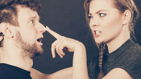 Woman applying cream to her man face. Protection and skincare. Stubborn girlfriend trying to apply cream on her boyfriend face. Man in uncomfortable situation Royalty Free Stock Image