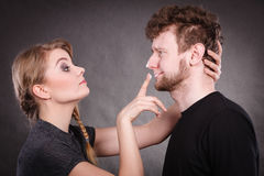 Woman applying cream to her man face. Protection and skincare. Stubborn girlfriend trying to apply cream on her boyfriend face. Man in uncomfortable situation Royalty Free Stock Photo
