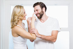 Woman applying cream to her man Stock Images