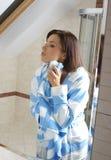 Woman applying cream to her skin Royalty Free Stock Photos