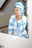 Woman applying cream to her skin Stock Photos