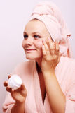 Woman applying creme on face Stock Photos
