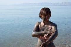 Woman applying Dead Sea mud body care treatment Stock Photos