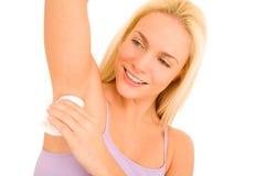 Woman applying deodorant Stock Image
