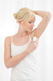 Woman applying deodorant Royalty Free Stock Photos