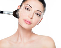 Woman applying dry cosmetic tonal foundation on the face royalty free stock photos