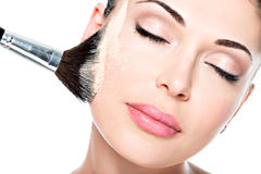 Woman applying dry cosmetic tonal foundation on the face stock photos