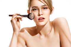 Woman applying dry cosmetic tonal foundation on the face using makeup brush. Royalty Free Stock Photos