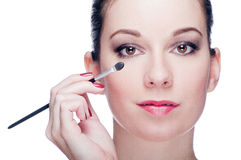 Woman applying eye make-up Stock Images