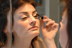 Woman applying eye makeup Stock Photography