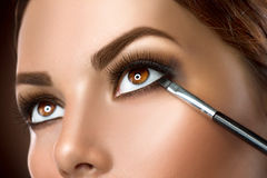 Woman applying eye makeup closeup stock image