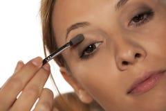Woman applying eye shadow Stock Image