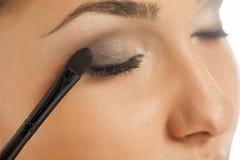 Woman applying eye shadow Stock Photos