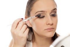 Woman applying eye-shadow Stock Photography
