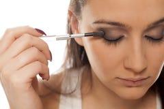 Woman applying eye-shadow Stock Images