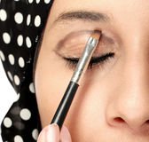 Woman applying eye shadows Royalty Free Stock Images