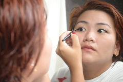 Woman applying Eyeliner Make-Up Stock Photography