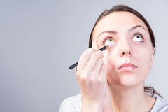 Woman Applying Eyeliner Makeup While Looking Up Royalty Free Stock Images