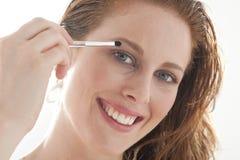 Woman applying eyeshadow Stock Photos