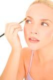 Woman applying eyeshadow Stock Image