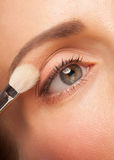 Woman applying eyeshadow Stock Photos