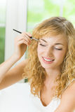 Woman applying eyeshadow Stock Photo