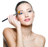 Woman applying eyeshadow with brush Stock Photo