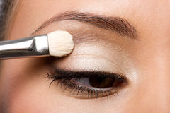 Woman applying eyeshadow on eyelid Royalty Free Stock Images