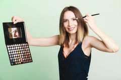 Woman applying eyeshadow with makeup palette Royalty Free Stock Photography