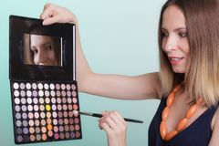 Woman applying eyeshadow with makeup palette royalty free stock photos